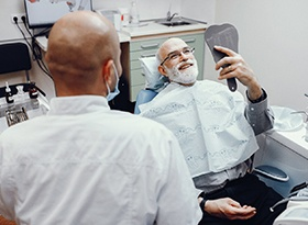 A man smiling at himself in the mirror at the dentist office