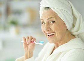 An older woman brushing his teeth