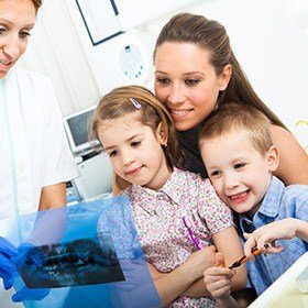 Mother and two children looking at dental x-rays