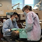 Dentist and team member treating patient
