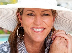 Smiling woman wearing large sun hat