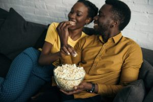 couple eating popcorn on their couch